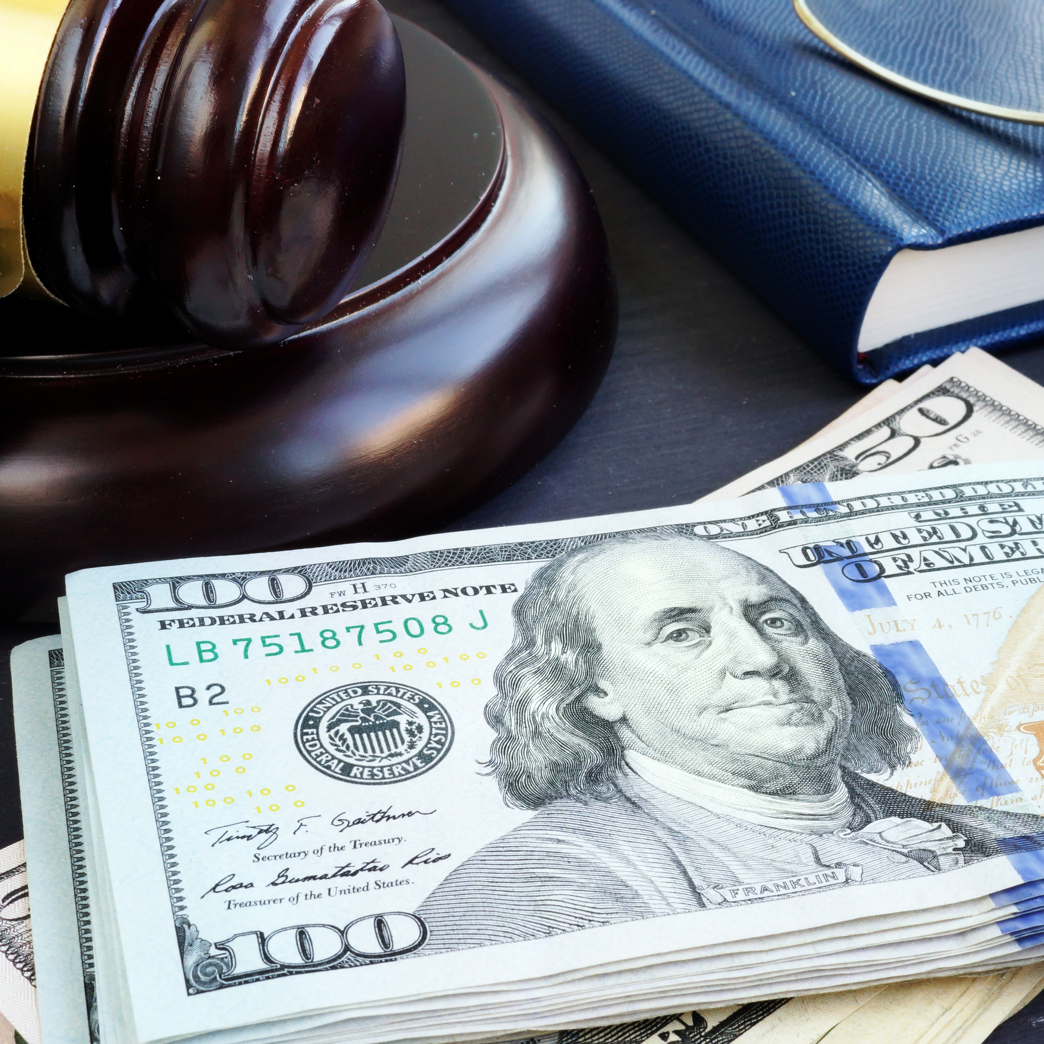 Money on a desk with a gavel in the foreground.