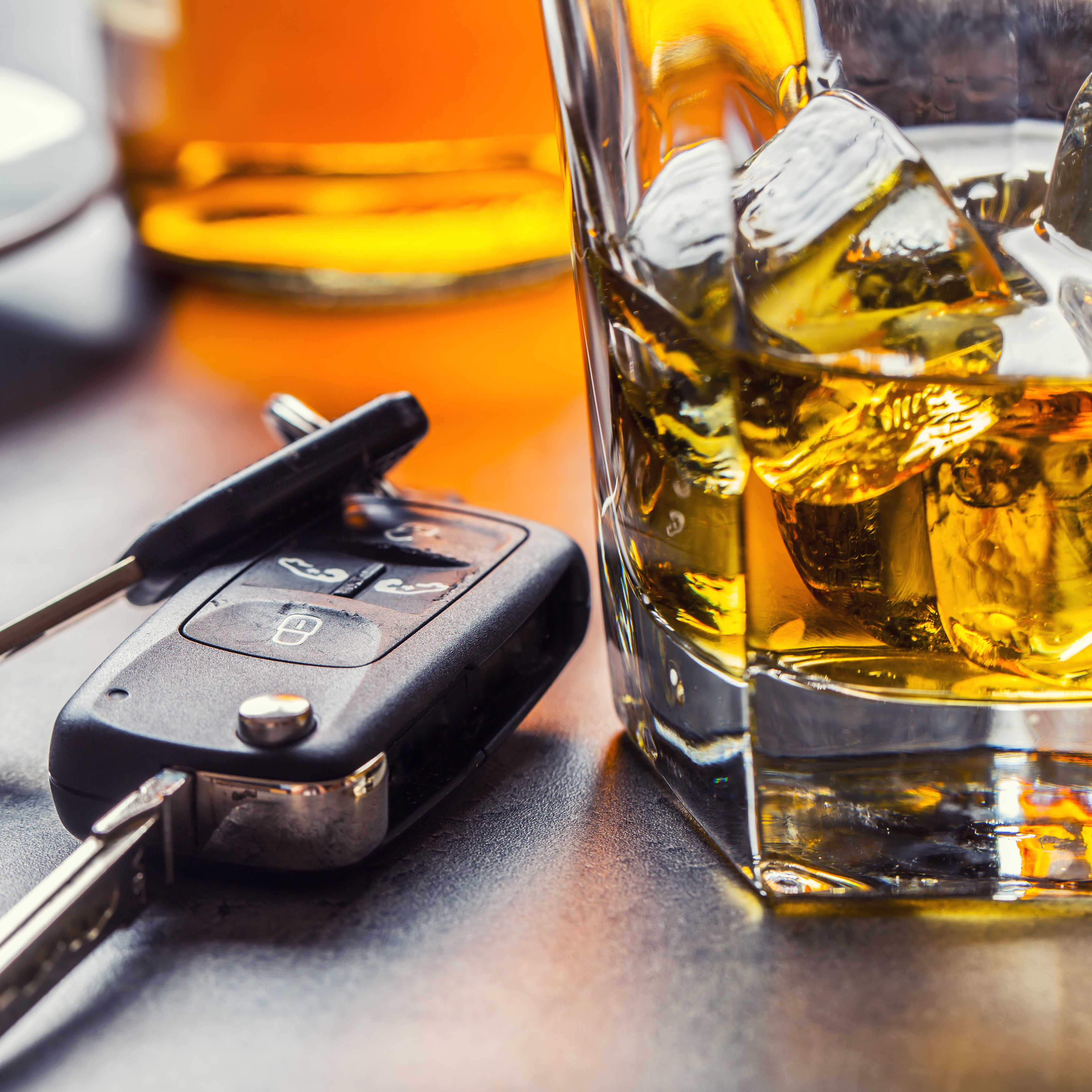 Car keys and a glass of alcohol on top of a table.